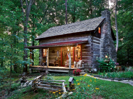 The vintage cabin, likely built in the 1800s, was overgrown with ivy when Jan Paul and Tammy Donelson discovered it. To restore the building, they tore ivy from the exterior and rebuilt the porch roof to make it more authentic to the period. The new porch features a standing-seam metal roof and new cedar posts cut from trees on the site. The landscaped path leads to the two-car garage and beyond that, to the main house.