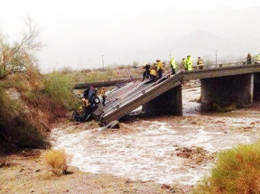 Rescue crews work to pull a pickup truck out of a rain-swollen wash that the truck fell into July 19 when the Interstate 10 bridge collapsed. :Photo:courtesy of Quartzsite Fire and Rescue